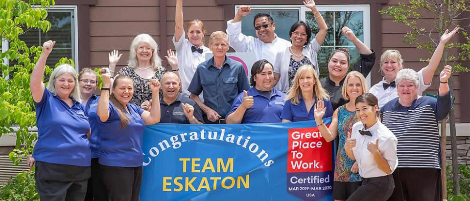 Eskaton staff holding a sign that says Congratulations Team Eskaton - Great Place to Work Certified March 2019 - March 2020 USA