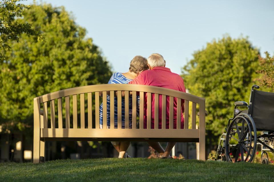 Couple sitting on a bench in a park at sunset