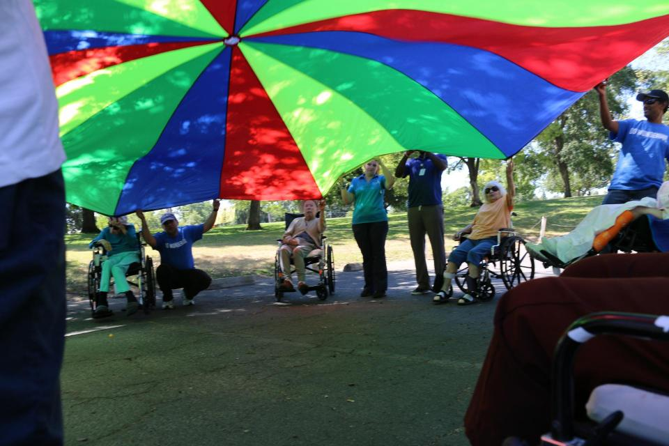 Staff, volunteer and residents in wheelchairs playing with a large colorful parachute