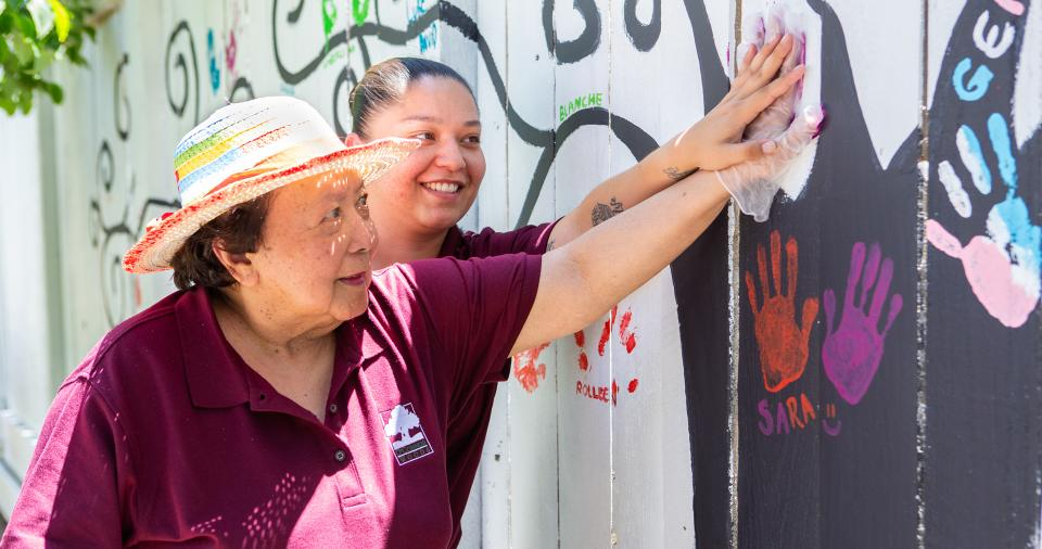 Resident putting her painted hand-print on the memory care fence with staff assisting her.