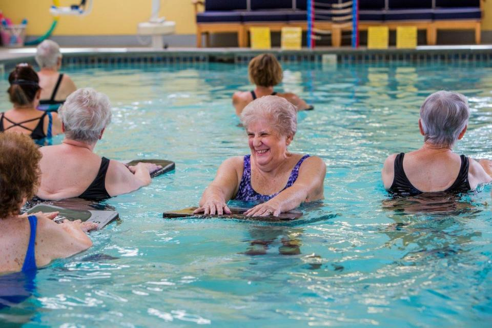 Several residents in the indoor pool enjoying a water aerobics class