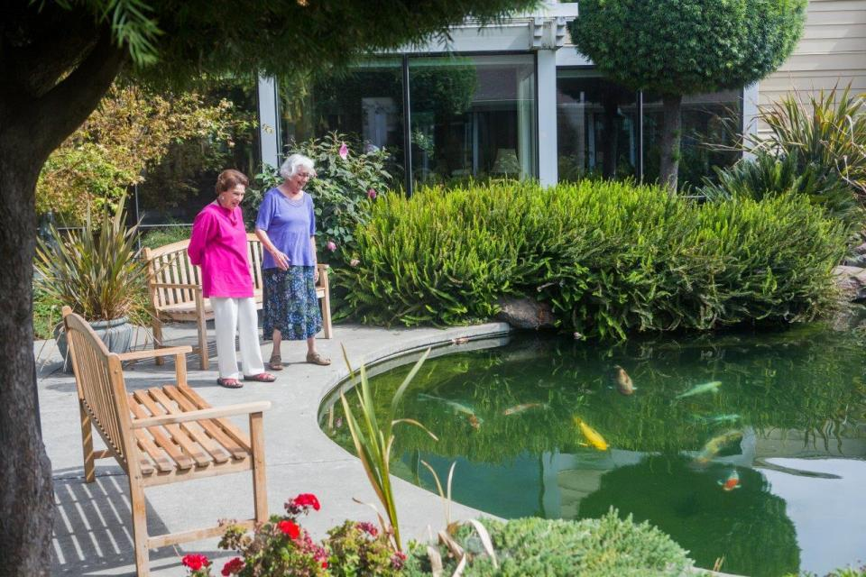 OCW-two women standing by the Koi pond feeding the fish
