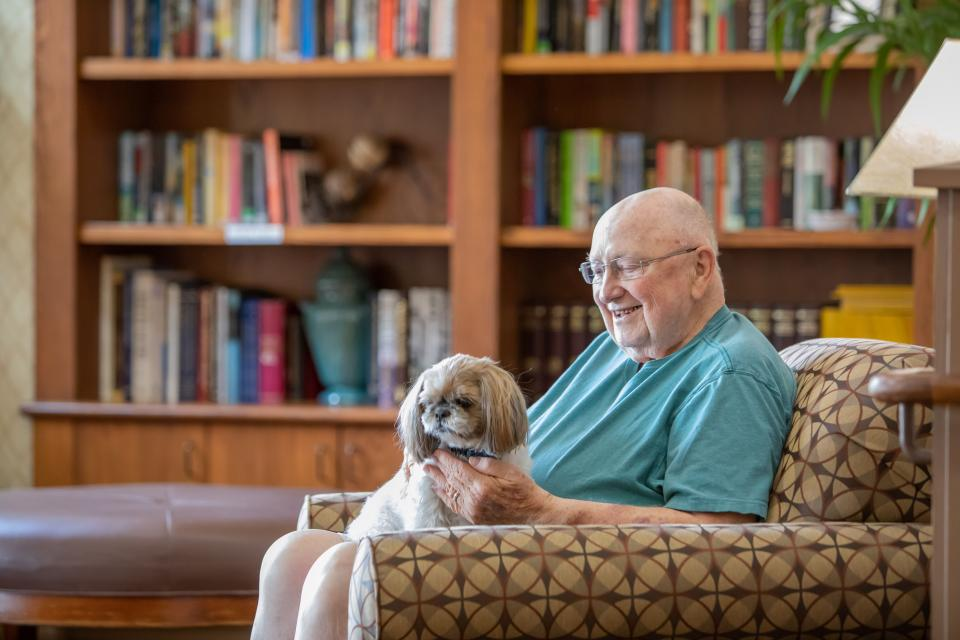 A smiling man sitting in the community library with his dog on his lap.