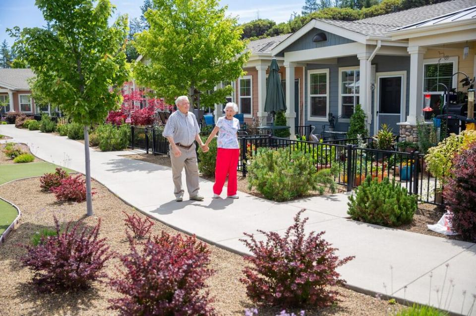 A smiling couple holding hands,  walking along the patio homes walking path