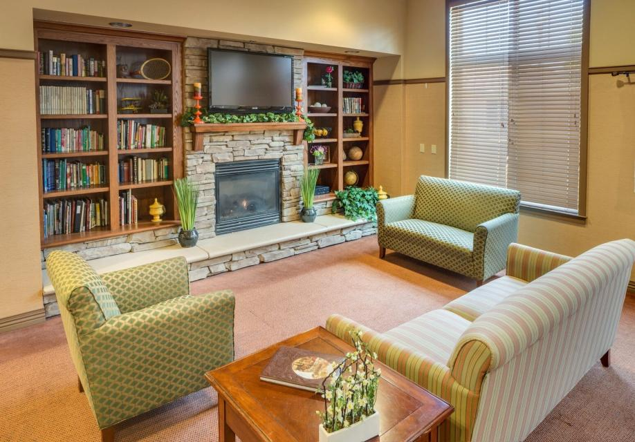 Lobby area with couch, love-seat, chair, fireplace and a entertainment center with books and TV