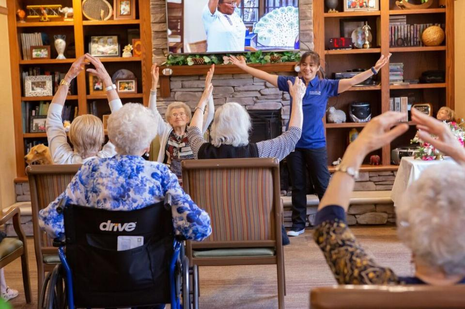 Staff member leading an exercise class with group of residents