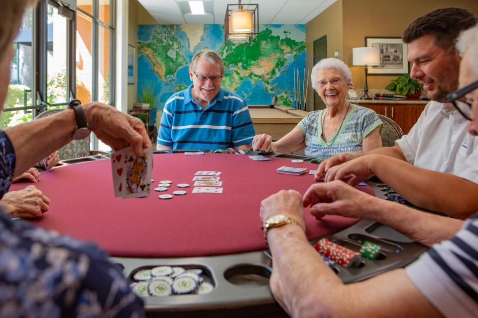 happy and smiling residents play a game of poker