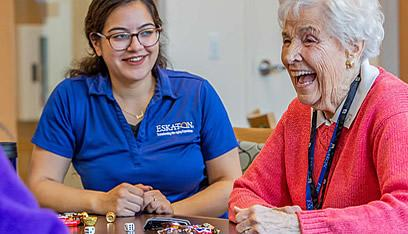 Resident and staff laughing and playing a dice game.