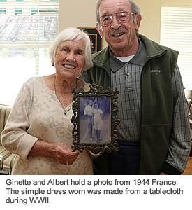 A resident couple smiling and holding a photo of themselves when they were 17 and 19 years old.