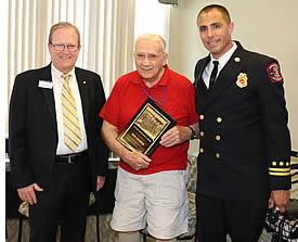 A resident being honored by the City of  Pleasanton's Major and Pleasanton Fire Battalion Chief.