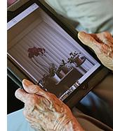 A resident holding their iPad, looking at photos.