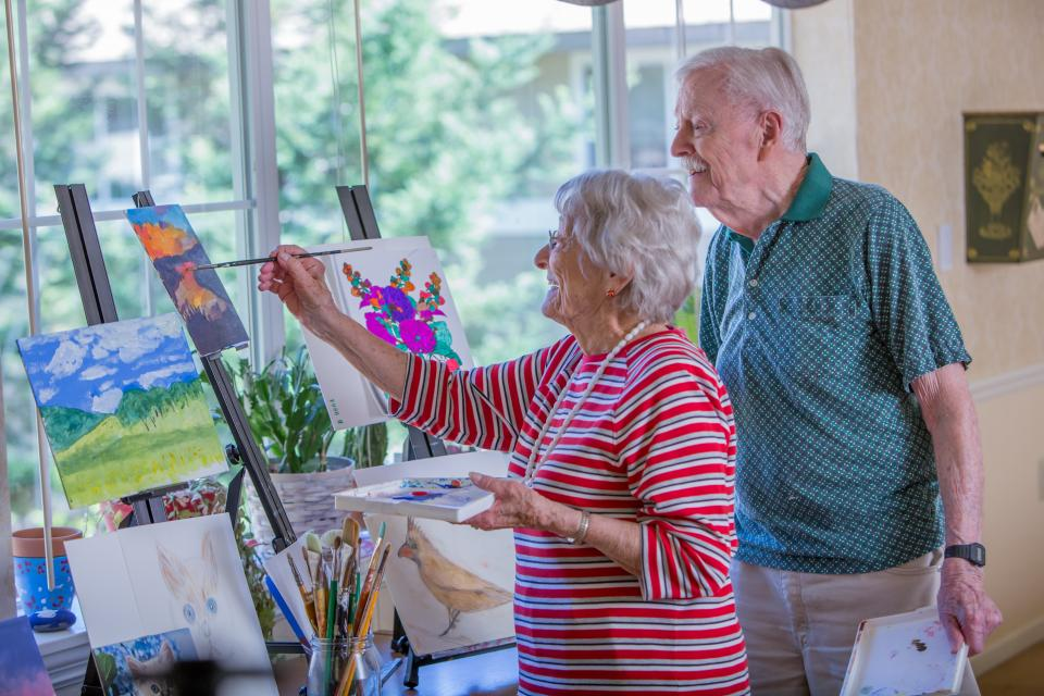 Male and a female resident painting on canvas