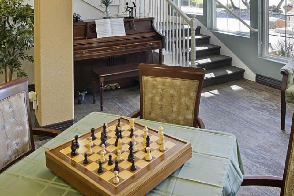 A game room with a chess game setup on a table and piano in the background