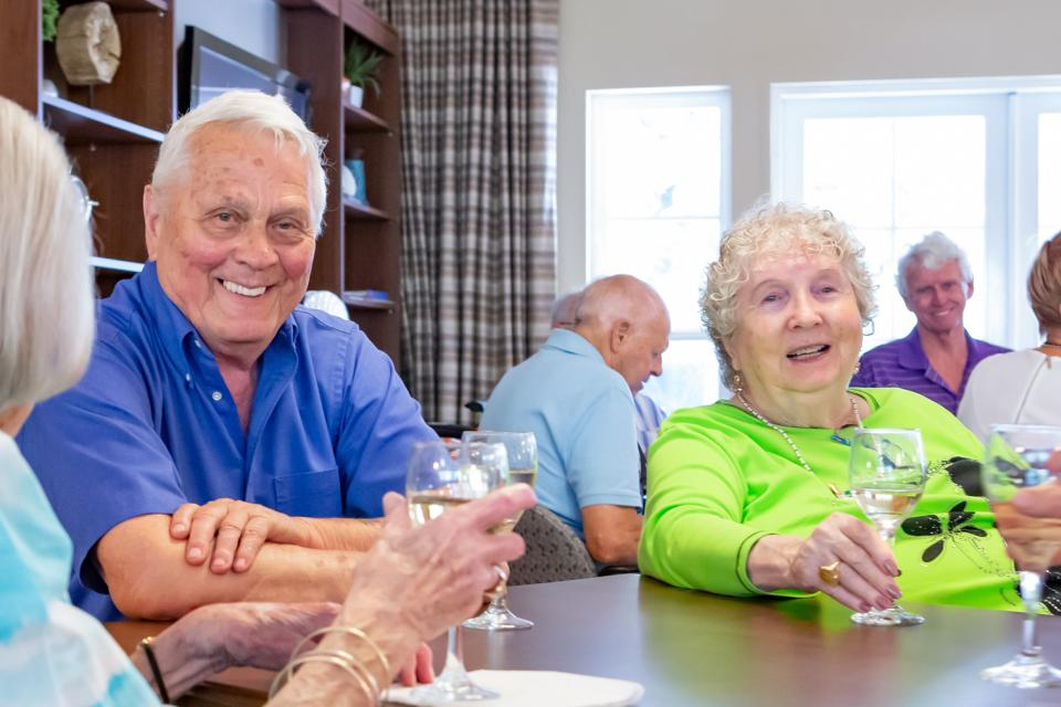 Residents enjoying a glass of wine at a social event.