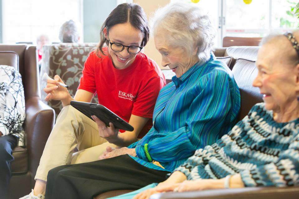 A staff member showing two smiling women residents something on an iPad