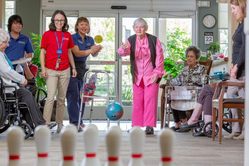 Resident woman throwing a bowling ball to knock down the bowling pins, with other residents and staff cheering her on.