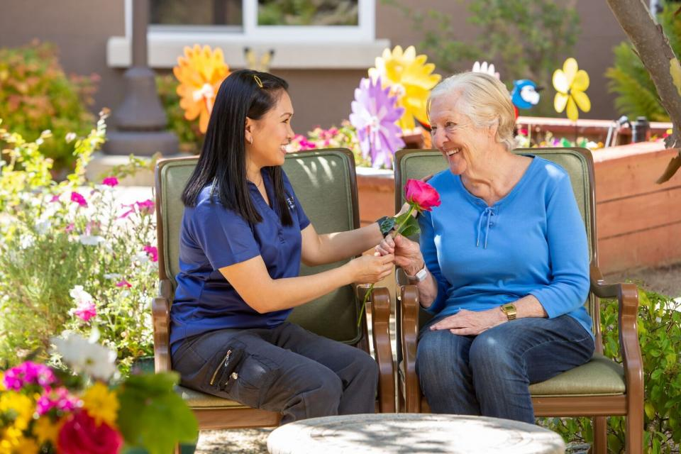 two women sitting by the garden. One woman giving the other a beautiful red rose.