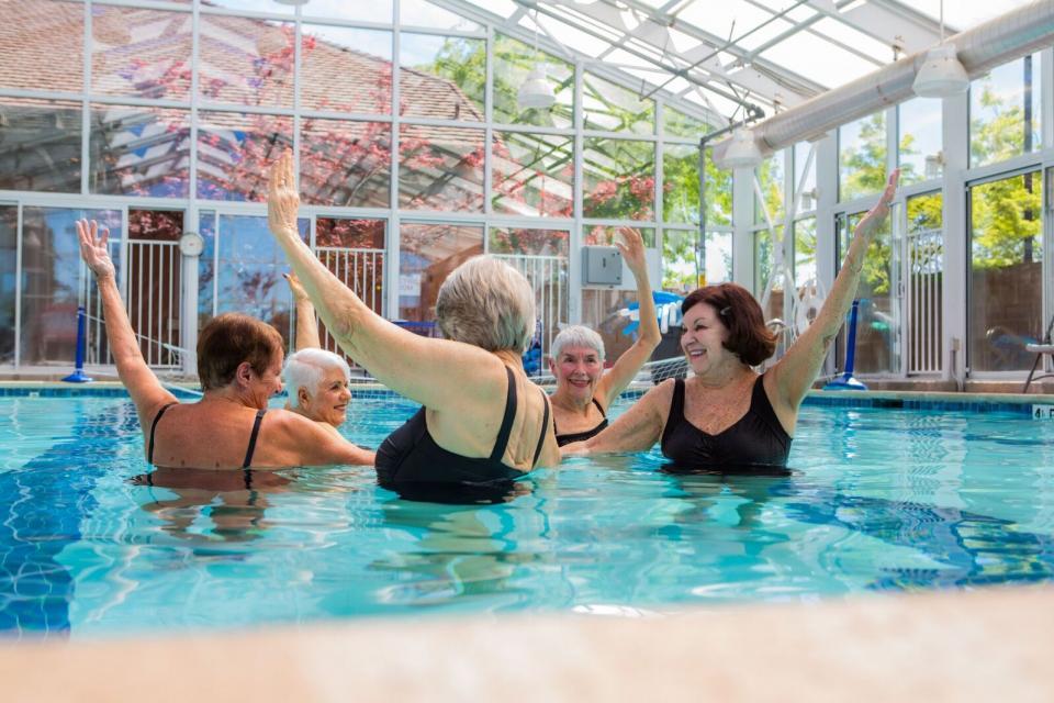 Four women in the in-door pool doing water aerobics.