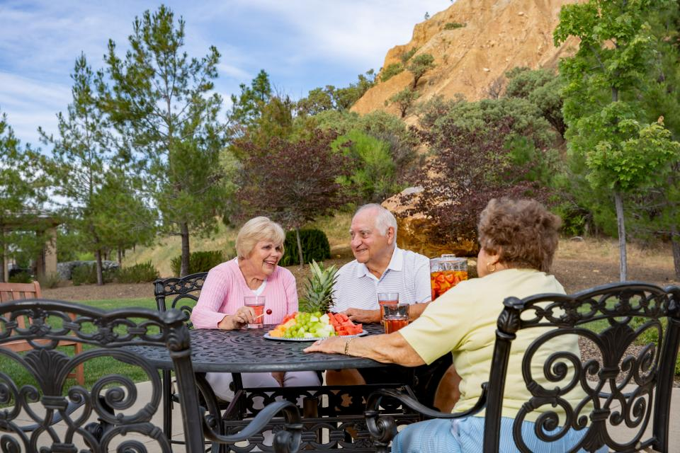 Two women and one man sitting at a patio table socializing with drinks and  a fruit