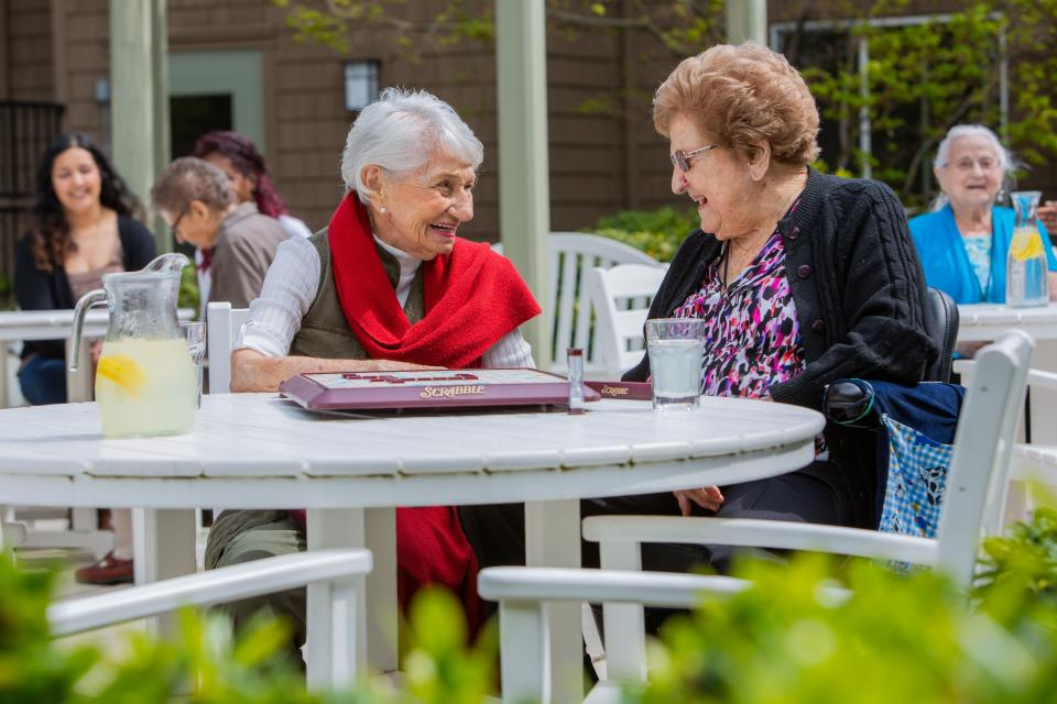 Residents sitting outside on the patio smiling and talking to each other.