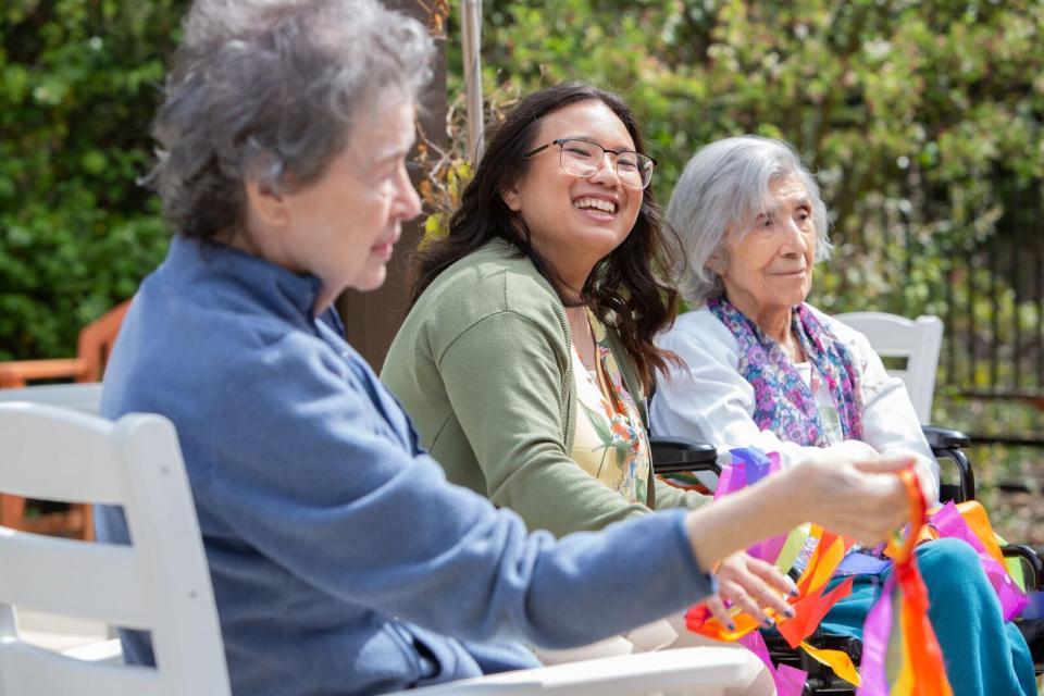 Three smiling women sitting outside.