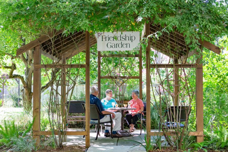 three residents sitting in the Friendship Garden's gazebo