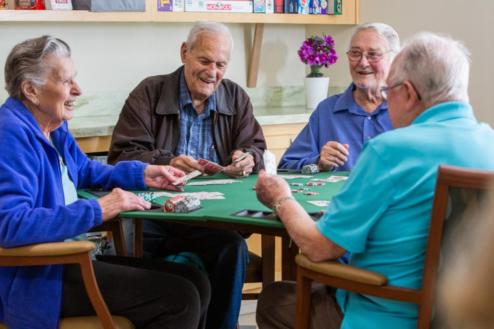 Four residents smiling and laughing and playing a game of cards