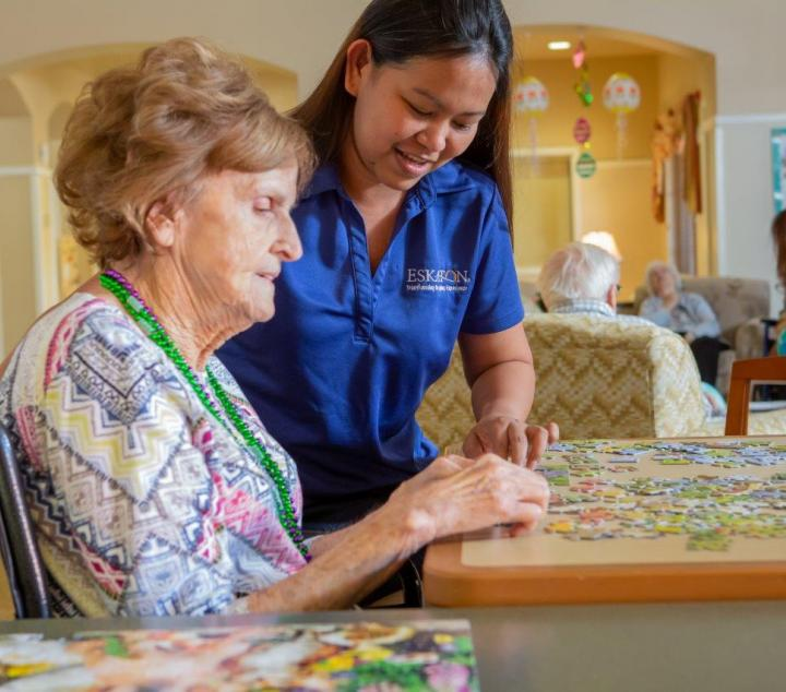 Resident and staff working on a puzzle