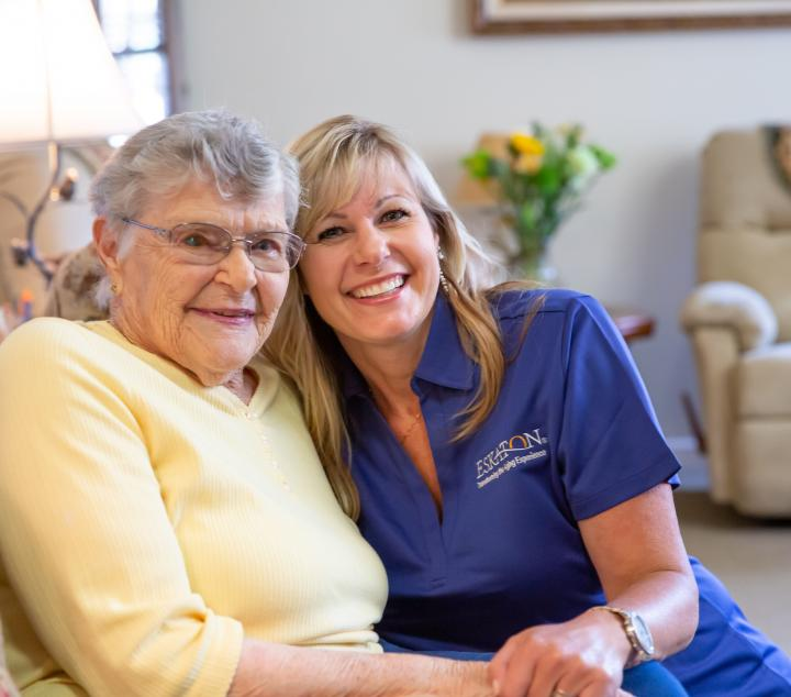 Two women, one a resident and the other a staff member smiling together.