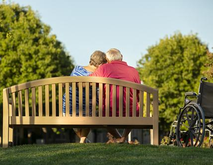 Couple sitting on a bench in a park at sunset.