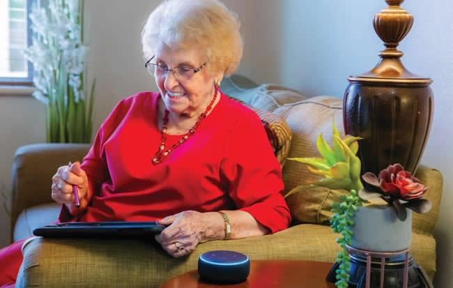 A smiling woman resident sitting on her couch with her iPad and Alexa.