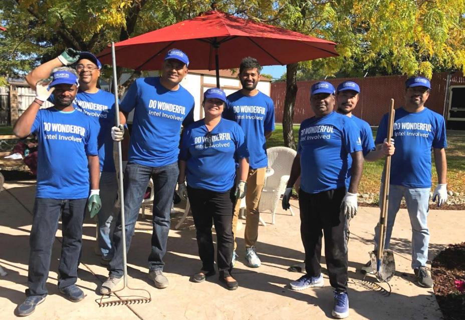 "A group of volunteers from Intel  wearing the t-shirts ""Do Wonderful Intel Involved"" with racks and shovels"