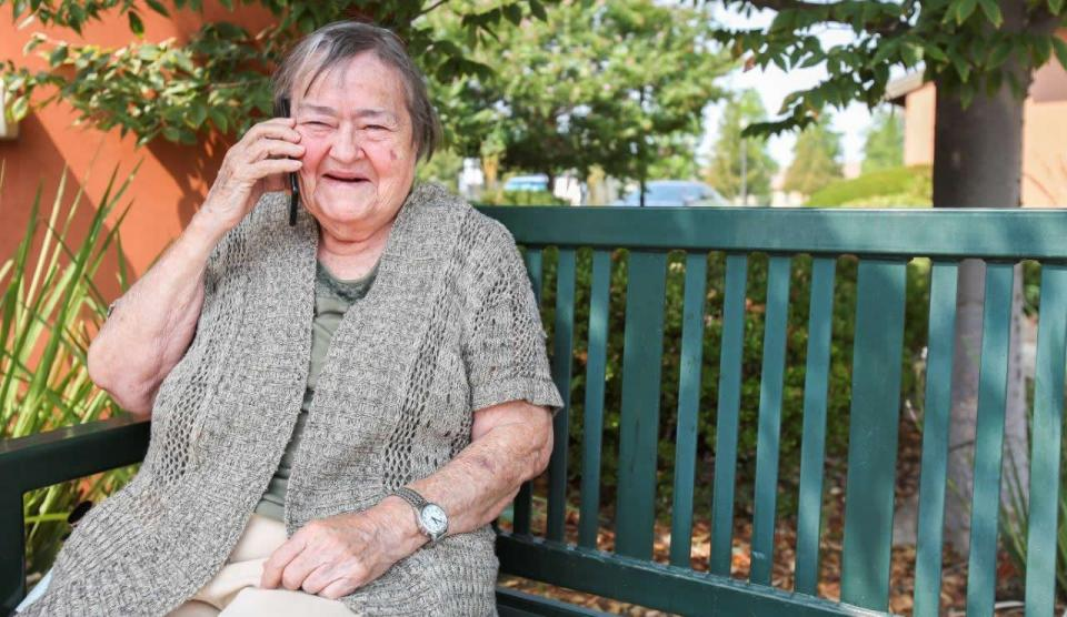 Smiling woman sitting outside on a green bench talking on a mobile phone.