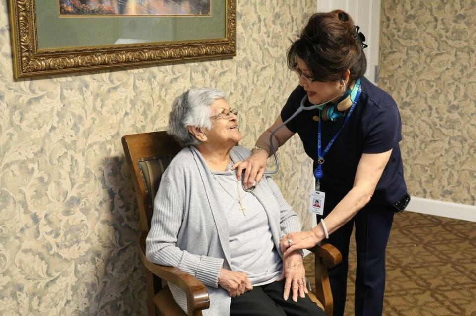 A nurse checking a woman's heart rate and pulse