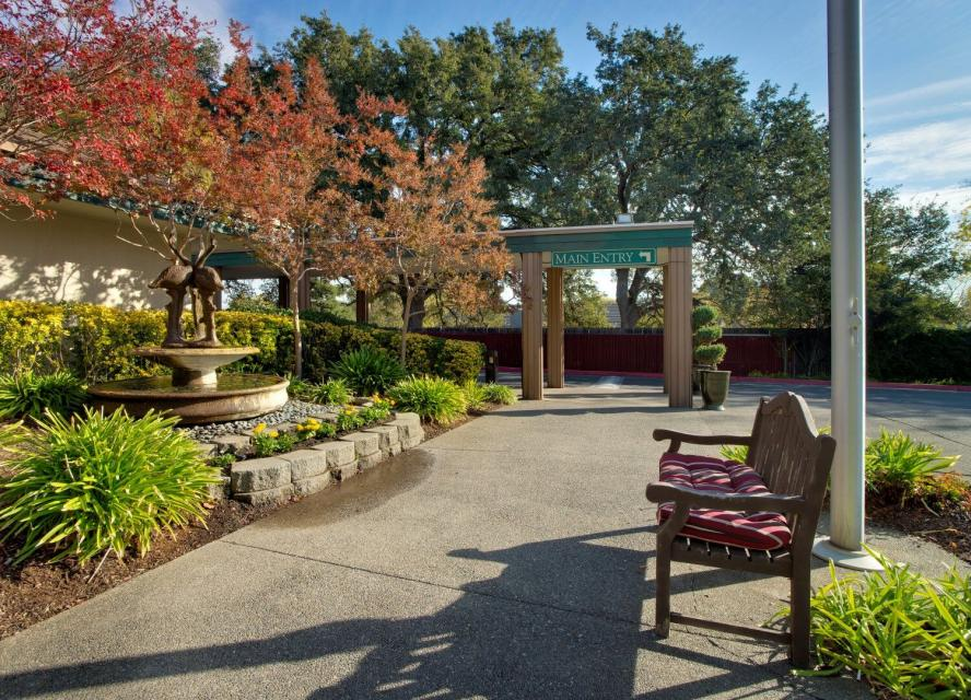 Eskaton FountainWood Lodge's side entrance with walkway, water fountain, bench and beautiful trees and bushes