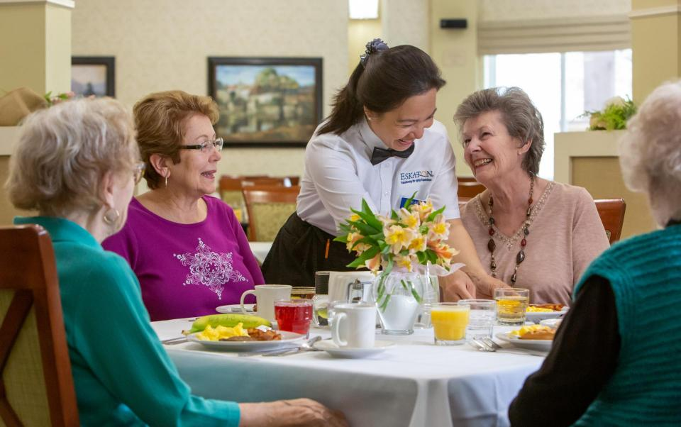 Residents dining and laughing with staff
