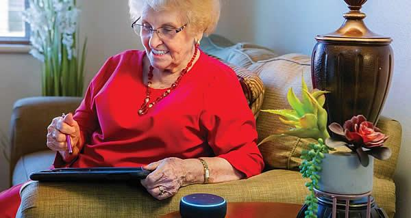 Woman resident sitting on her couch with her iPad and Alexa.