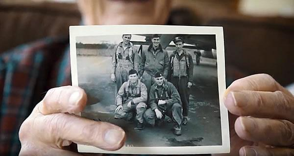 A resident veteran holding a photo of him and four of his air-force buddies.