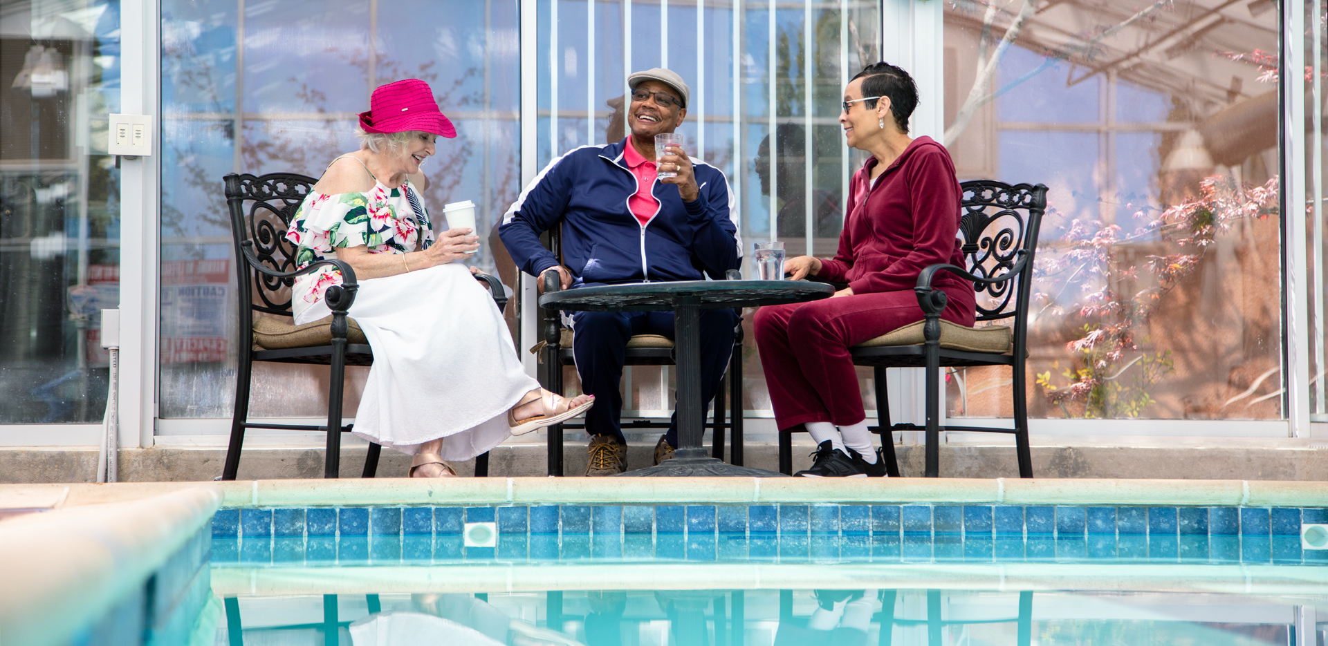 Three residents sitting at a patio table, talking and laughing, around the pool